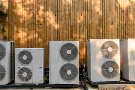 Many compressor air conditioning working on wooden wall at outside
