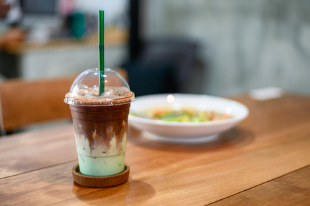 Beverage ice dark chocolate with green mint in plastic glass on wood table Imagens