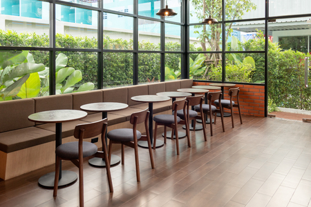 Phuket, Thailand - Dec 12 2018 : Rows of wooden table and chair inside of glass room with green garden