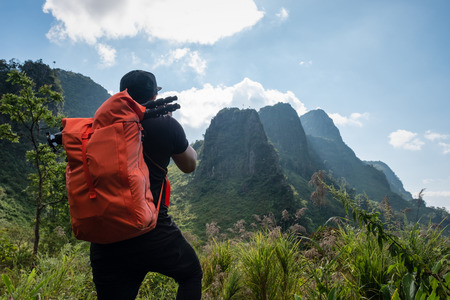 Man backpacker standing take a photo with tropical mountain on peak
