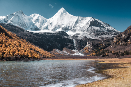 Holy mountain yangmaiyong with frozen river in autumn valley at Yading nature reserve Stock Photo