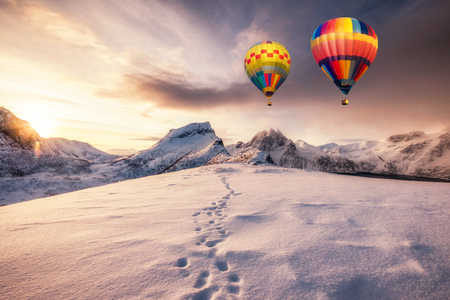 Hot air balloons flying on snowy mountain with footprint on peak at sunrise Stockfoto