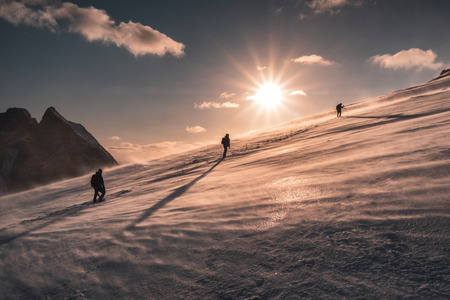 Alpinisti che scalano nella bufera di neve sulla collina innevata al tramonto. Ryten montagna Archivio Fotografico