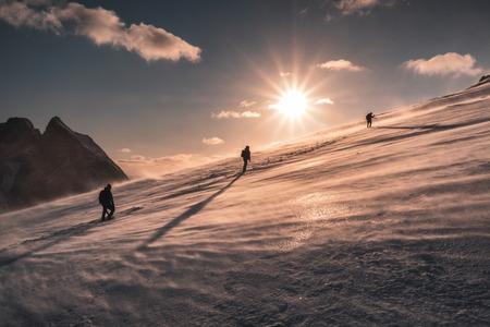 Bergbeklimmers klimmen in blizzard op besneeuwde heuvel bij zonsondergang. Ryten berg Stockfoto