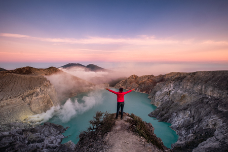 Woman standing on ridge in active volcano with smoke of sulfur in morning at Kawah Ijen