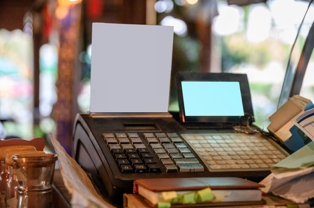 Cashier counter with digital screen and white label on wooden table in restaurant