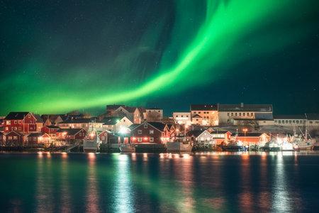 Northern lights over fishing village on coastline at Lofoten, Norway Editorial