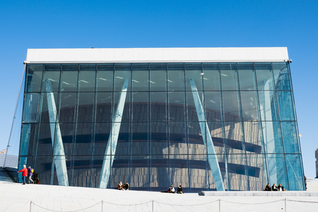 Oslo, Norway - Mar 27 2018 : Architecture building with blue glass and tourists traveling and relaxation at Opera House landmark