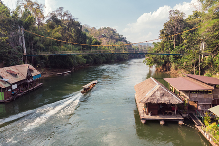 Wooden boat sailing on river with tropical wooden village at national park