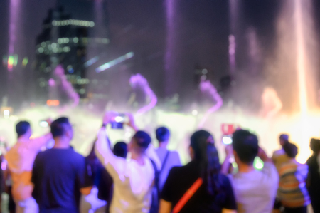 Blurred scene people seeing show of laser light with fountain event in the city