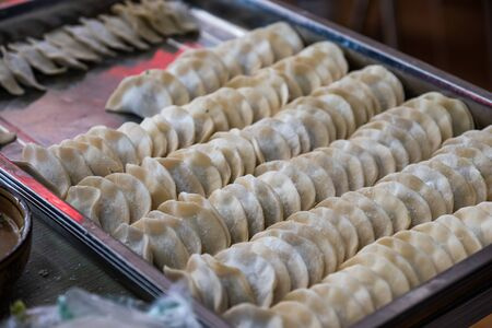 Yellow rows dumplings filling vegetable on tray