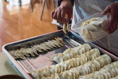Hand picking yellow dumplings filled sorted on tray