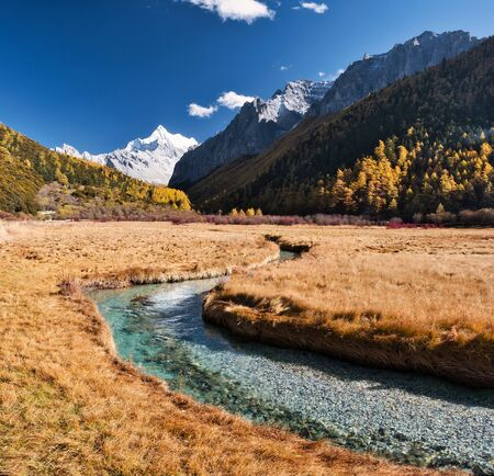 Chana Dorje holy mountain with golden meadow and crystal river in autumn valley at Yading nature reserve 스톡 콘텐츠