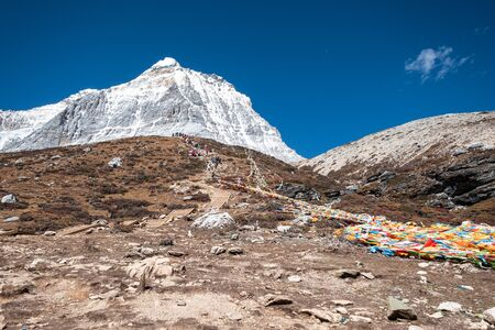 Landscape of limestone mountain with colorful prayer flags and blue sky near milk lake at Yading nature reserve 스톡 콘텐츠