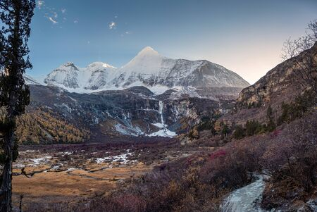Holy mountain Yangmaiyong with autumn forest at evening. Yading nature reserve, Daocheng, China