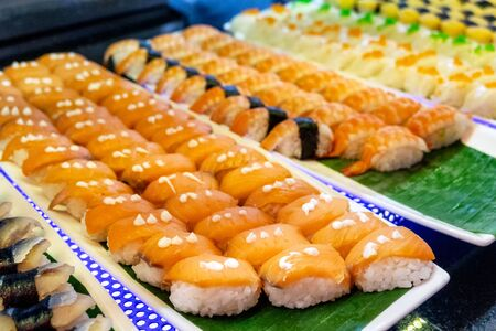 Sorted of variety sushi with salmon fish, shrimp, egg with rice on tray in restaurant