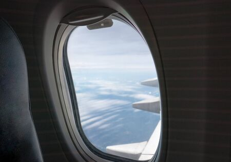 Window side of passenger with wing airplane flying on sky