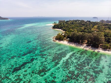 Aerial view of coral reef in emerald sea at lipe island