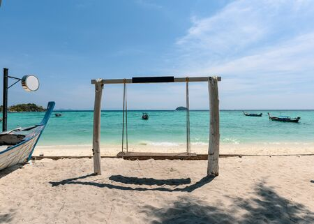 Wooden swing on the beach with long-tail boat in tropical sea at lipe island 版權商用圖片 - 134877486