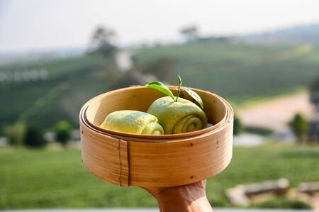 Green tea steamed bun on wooden basket in tea plantation background