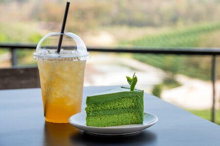 Green tea cheesecake with ice thai tea drink on wooden table Reklamní fotografie