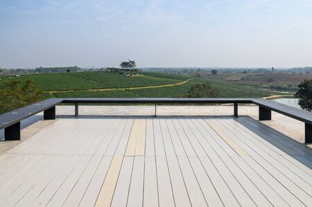 Bench on wooden patio of roof with tea plantation view
