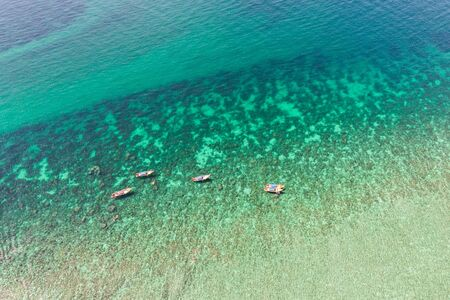 Aerial view Wooden long-tail boats sailing on turquoise sea at Lipe island