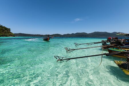 Wooden long-tail boats anchored on turquoise water in tropical sea