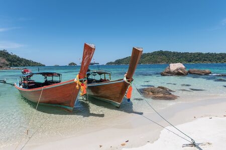Wooden long-tail boats on crystal tropical sea at Lipe island