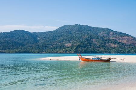 White sand beach with wooden long-tail boat in tropical sea at Lipe island