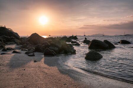 Rocks on coastline with yacht at sunset shine