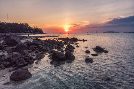 Rocks on coastline in tropical sea at sunset