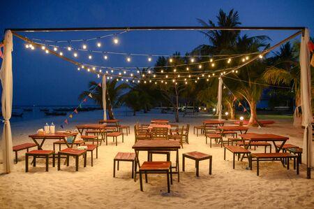 Set dining table with illumination shine on the beach