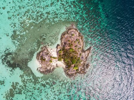 Aerial view of island with coral reef in tropical sea