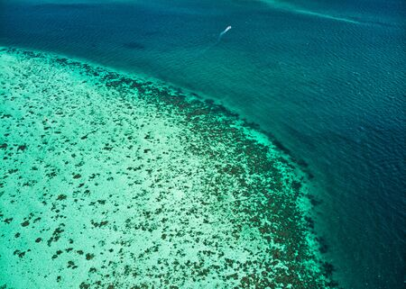 Aerial view of Tropical emerald and blue sea with coral reef and ship sailing Reklamní fotografie - 134746498