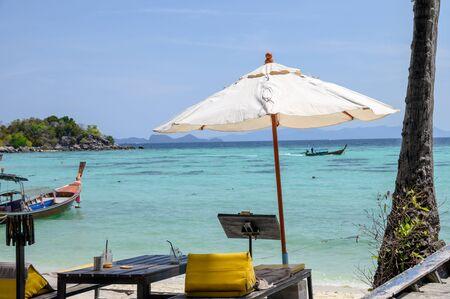 Sunbed umbrella on tropical sea with wooden boat Reklamní fotografie - 134746499