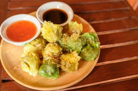 Yellow and green dumpling dim sum stuffed with pork and shrimp with sauces on wooden tray