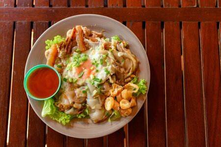 Stir-fried rice noodle with chicken, squid, fry egg and lettuce on plate Reklamní fotografie - 134790665