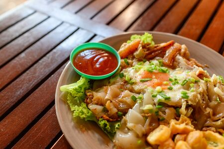 Stir-fried rice noodle with chicken, squid, fry egg and lettuce on plate Reklamní fotografie - 134790666