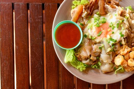 Stir-fried rice noodle with chicken, squid, fry egg and lettuce on plate Reklamní fotografie - 134790667