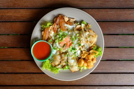 Stir-fried rice noodle with chicken, squid, fry egg and lettuce on plate Reklamní fotografie