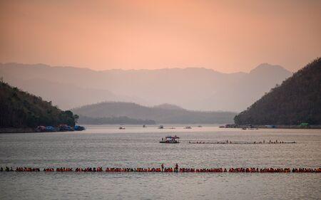 Kanchanaburi, Thailand - Apr 06 2019 : Tourists on long wooden raft floating on Srinakarin dam and mountain at sunset Reklamní fotografie