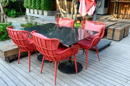 Marble dining table with red weave chairs with pillow on wooden patio Reklamní fotografie