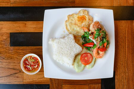 Stir-fried basil, chili with shrimp, squid with fried egg and white rice on plate Reklamní fotografie - 134790884