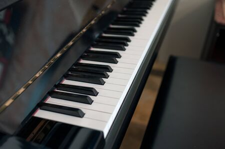 Classical piano keyboard with seat. Side view