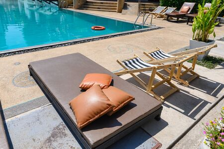 Mattress bed with wooden sunbeds on side of swimming pool and garden