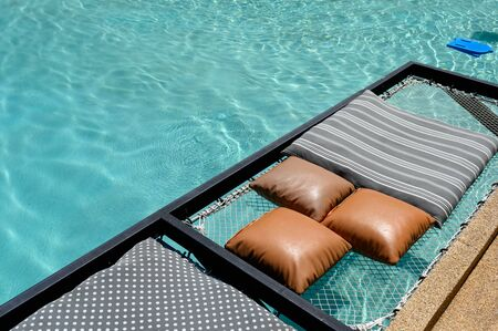 Relaxation mesh seat with pillows jut out on swimming pool Reklamní fotografie