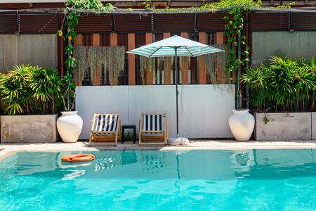 Wooden sunbeds with parasol and ornamental garden on swimming pool