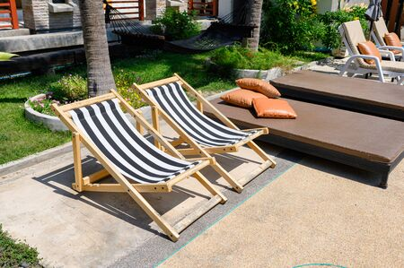 Wooden sunbeds with mattress on side of swimming pool with garden