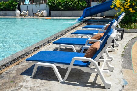 Blue sunbeds with mattress on side of swimming pool in hotel